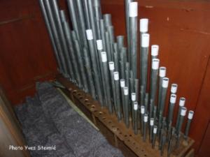 L'orgue à l'origine était accordé au diapason 435 (la 3). Au cours des années il a été accordé à 440 donc les tuyaux ont été raccourcis. Pour rétablir l'accord le facteur d'orgue doit rallonger les tuyaux de certains jeux. Ce que l'on voit en blanc sont des gabarits servant à fabriquer des manchons au bon diamètre et bonne longueur qui seront posés sur les tuyaux. On peut voir que les tuyaux sont posés sur un sommier. Il reste des emplacements pour une autre série de tuyaux.